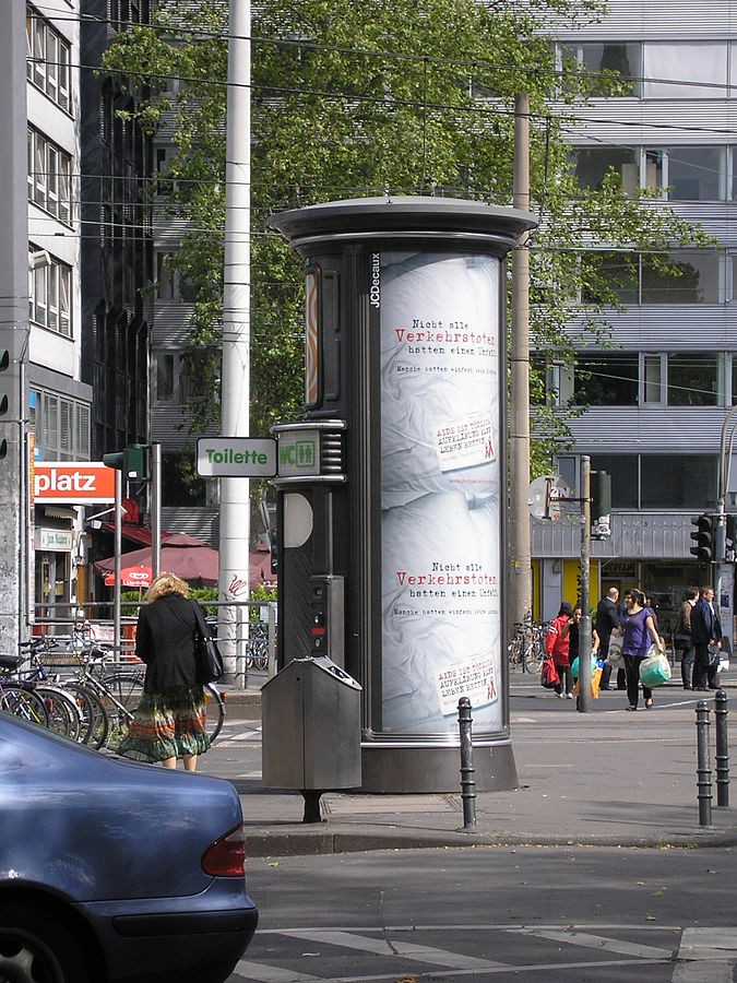 Farbenfroh und formschön: Ein in einer Litfaßsäule verstecktes Klohäuschen am Barbarossplatz, Bild: Duhon [CC BY (https://creativecommons.org/licenses/by/3.0)]